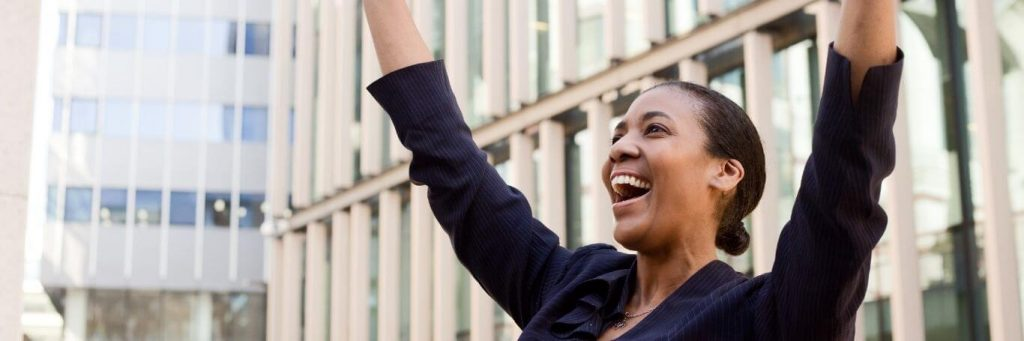 woman happy exciting celebrates tall business buildings
