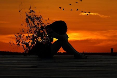 woman shadow sadly sits crying in red sunset sky