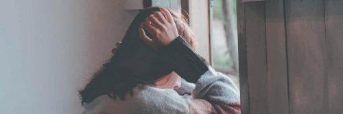 girl hands on head face downward sits beside window feeling sad