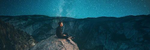 man sitting on on rock watching blue star sky