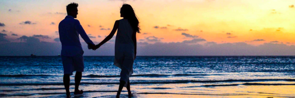 couple hand in hand happily walks along beach in sunset sky