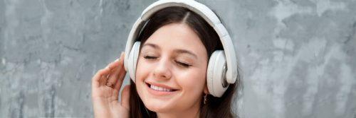 young woman wearing headphone enjoying listening to music
