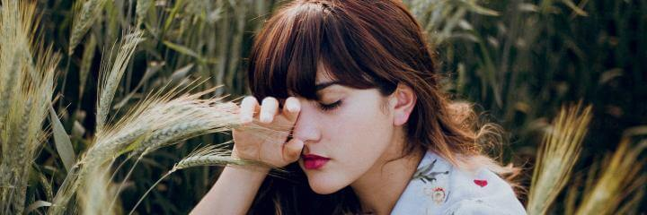 woman sits beside trees closing eyes thinking feeling overwhelmed