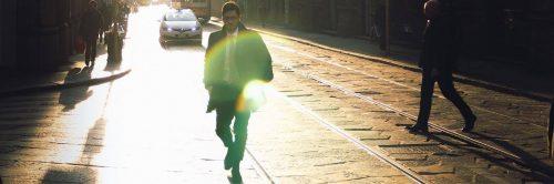 businessman walks alone on street beside railway