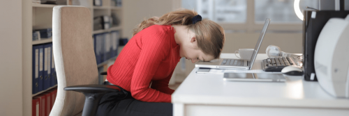 woman head on laptop distressed feeling tired in office room
