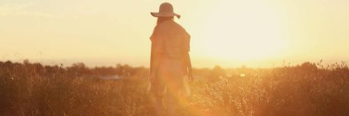 woman facing backward stands on field walking in beautiful sunny sky