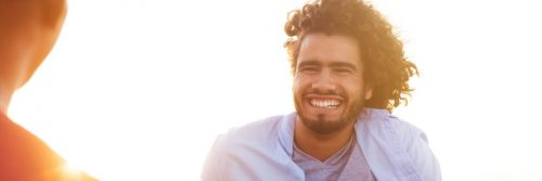 curly hair man smiles in sunny sky