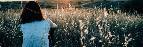 woman sits on field facing backward looking at sunny sky