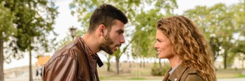 couple argues in forest man trying to explain while woman angrily listening looking at him