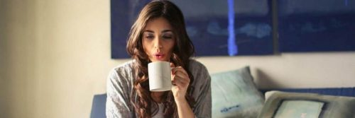 woman sits on couch holding white mug blowing