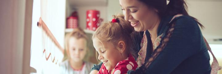 woman happily plays with daughter while another little girl sitting looking at home