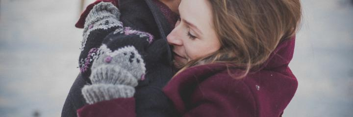 woman wearing gloves jacket hugging another person