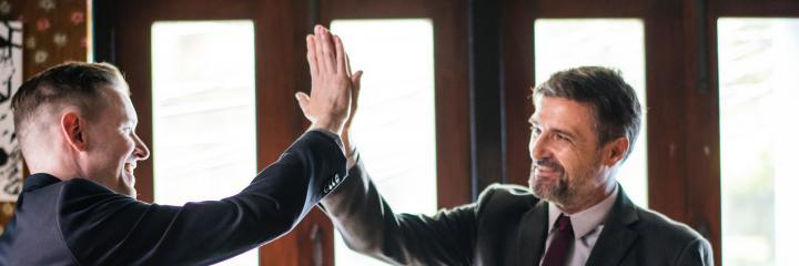 two businessmen clap hands celebrating success