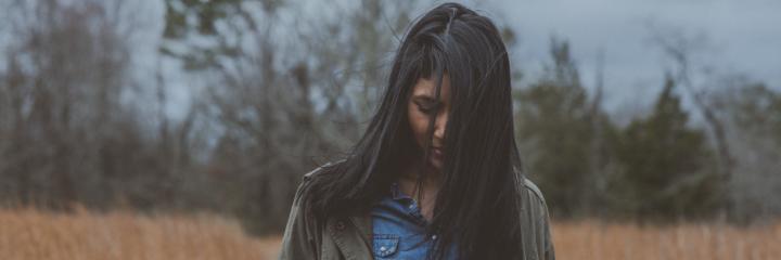 woman stands alone on field feeling sad