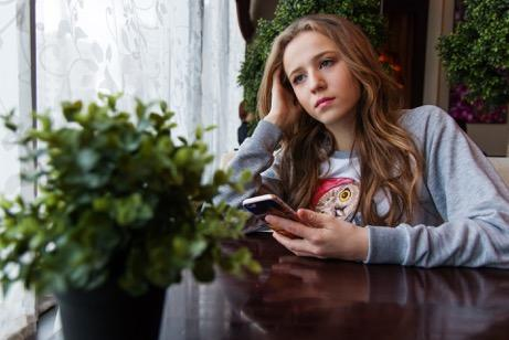 Girl on her phone at a table, looking sad.